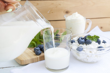Pouring milk in the glass on the table with other dairy products, bilberry and fresh mint