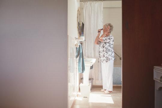 Elderly woman getting ready in bathroom
