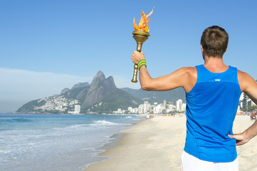 Torchbearer athlete standing with sport torch above the Rio de Janeiro, Brazil skyline at Ipanema Beach