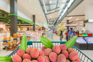 ripe litchi fruits in shopping trolley in supermarket