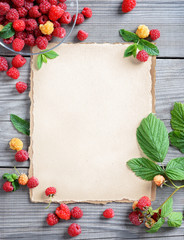 Organic berries background. Open recipe book with raspberries on wooden table. Copy space, top view, high resolution product.