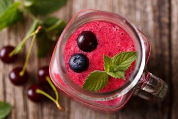 Top view on healthy berry smoothie in glass jar.