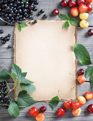 Healthy and fresh berries background. Old paper with fresh cherries and currants on wooden table. Copy space, top view, high resolution product.