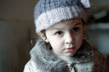 Portrait of young girl indoors, wearing wooly hat