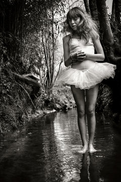 Young girl, wearing tutu, standing in stream, black and white