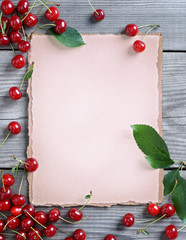 Healthy eating concept. Old paper with ripe cherries on wooden table. Copy space, top view, high resolution product.