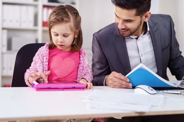 kind spielt am tablet während papa arbeitet