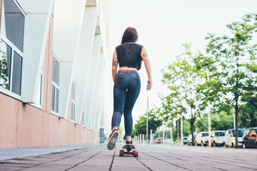 Rear view of a young woman riding skateboard on footpath
