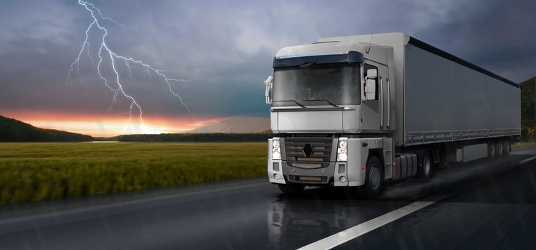 The white truck travels on the road in the rain.