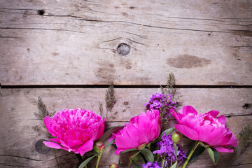 Border from  pink peonies flowers on aged wooden background