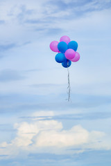 balloons on the cloudy day, pink and blue balloons with blurred sky background and copy space, hope and dream on the blue day concept
