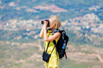 Female traveler stands on a hill and looks over the valley bottom and takes pictures. Woman enjoying the views from the top of the mountain and make a photo.