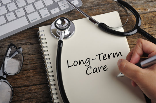 "Women Hand Write ""LONG-TERM CARE"" On Note Book"