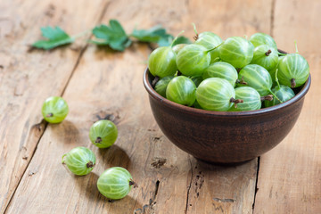Fresh green gooseberries in clay bowl on table close-up