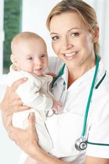 Portrait Of Nurse Holding Baby Girl