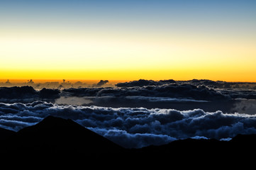 Spectacular view before sunrise on the summit of Haleakala Crater (10,023 ft) on the island of Maui, Hawaii. Impression of an ocean of clouds. One of Maui's most famous tourist attractions.