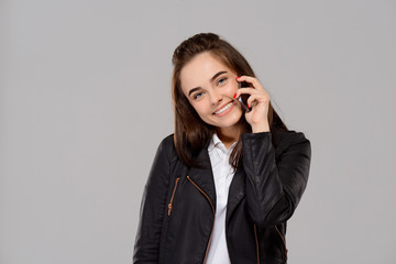 Young beautiful girl speaking on phone, smiling over purple background.