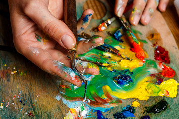 Close up photo of girl mixing oil paints on palette.
