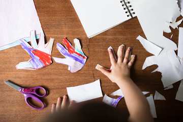 Small child drawing and cutting hands from paper
