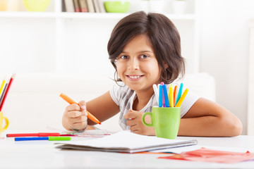 Sweet little girl sitting at desk and draw with  color pencil.She looking at camera and smiling.