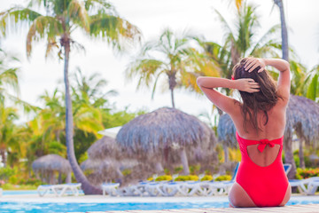 young woman with flower in hair enjoyng sunny day in luxury pool