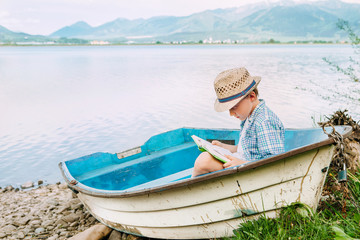 Boy with book seats in old boat on the lake bank