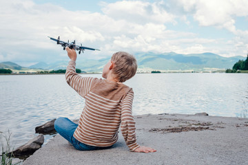 Boy play with toy plane sitting near the lake
