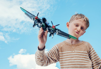 Boy play with model military plane
