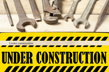 Under construction board with repair tools. Wrench on wooden background