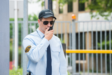 Security Guard Talking On Walkie-talkie