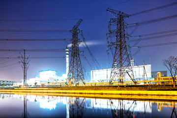 pylons near power plant at night from water