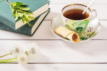 Cup of tea, cookies, stack of books and dandelions on a white wooden background