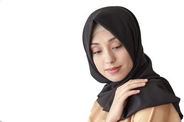 Studio portrait of a young woman in traditional Muslim dress and black scarf on her head, isolated on white background