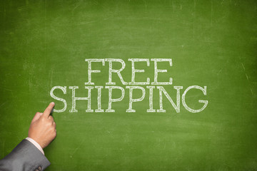 Free Shipping text on blackboard with businessman hand pointing