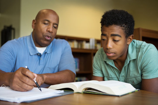 Portrait of teacher assisting a teenage student with homework in the library.