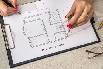 woman paints a house plan