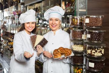Happy saleswomen with chocolates.