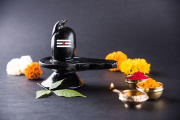 Shiva Linga made up of black stone decorated with flowers & bael leaf known as Aegle marmelos, over black background, maha shiva ratri a festival of hindu God shankar or shankar bhagwan or bholenath