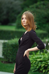 Stylish young fashion model in black overall with deep decollete in city park