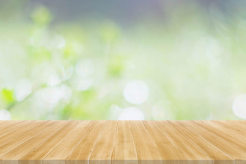 Wood table top on green bokeh abstract background - display your products
