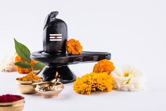 Shiva Linga made up of black stone decorated with flowers & bael leaf known as Aegle marmelos, over black background, maha shiva ratri a festival of hindu God shankar or shankar bhagwan or bholenath