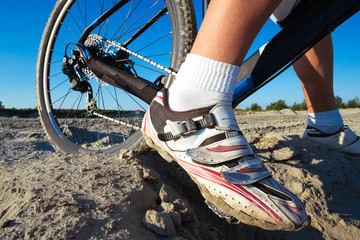 Detail of cyclist man feet riding mountain bike