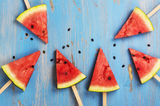Watermelon popsicles over blue wooden background
