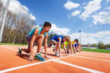 Fototapeta Five teenage athletes ready to run on a racetrack obraz