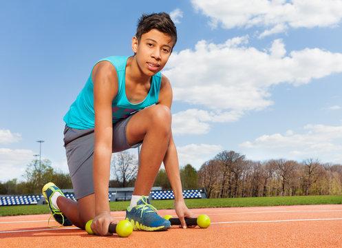 Teenage sporty boy picking up dumbbells in stadium
