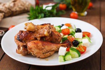 Appetizing oven baked golden chicken drumsticks and Greek salad