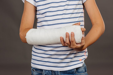 Close-up of a broken arm in a cast on striped shirt  background