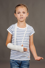 girl with broken arm  is standing and looking at the camera