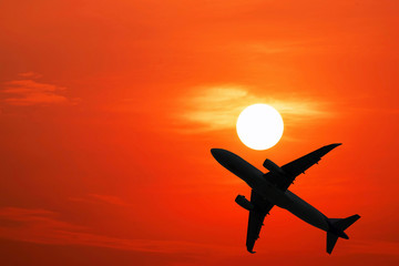 Silhouette airplane on the red sky with beautiful sunset.