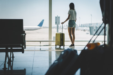 Young hipster girl standing near the window, looking on airplane while waiting flight, traveler woman standing at departure lounge with yellow suitcase, waiting for the arrival of the aircraft